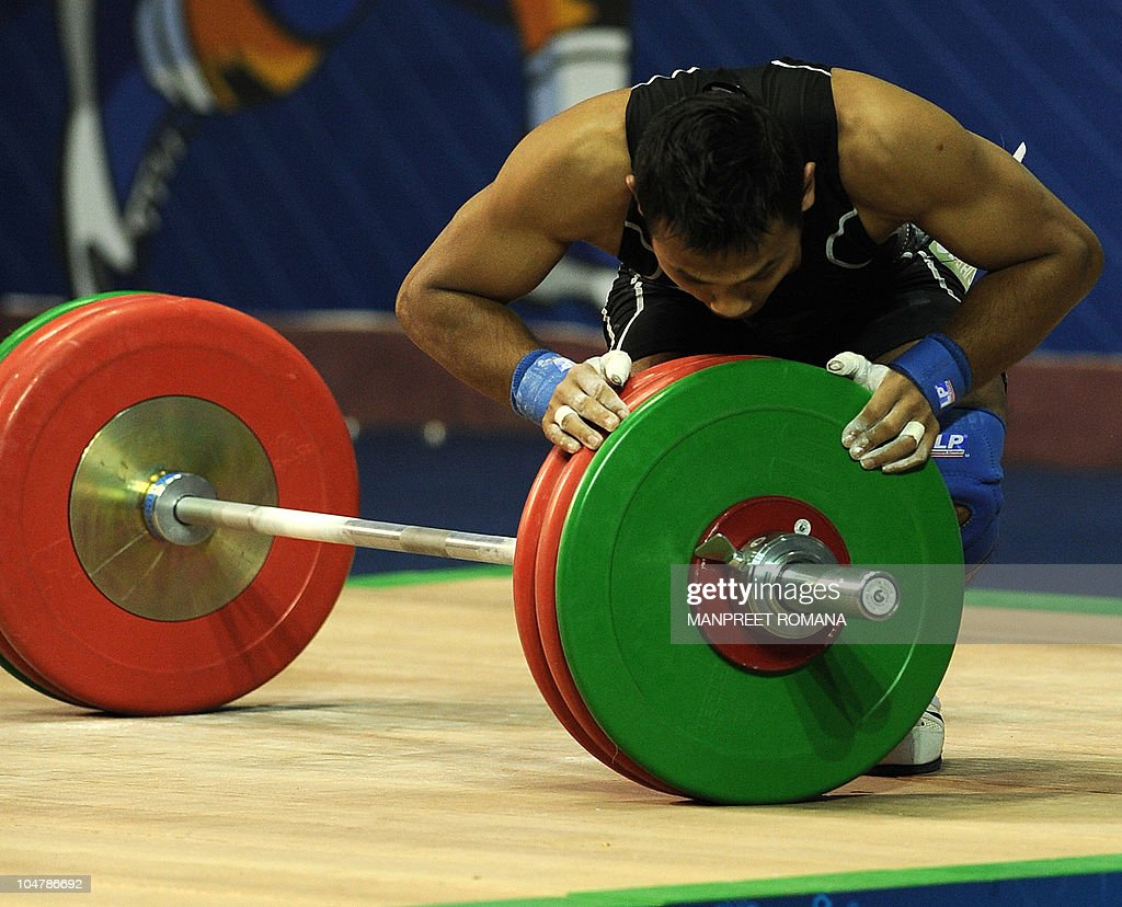 Malaysia's silver medal winner Naharudin Mahayudin kisses the weights after a succesful lift during the men's 62 kg weightlifting clean and jerk...