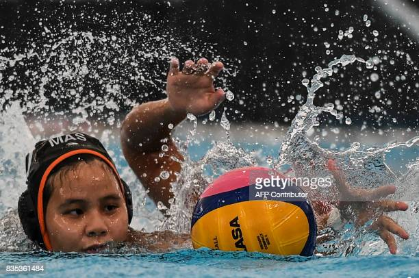 Malaysia's Trisha hen Chiah Huey is challenged for the ball by Indonesia's Hanna Firdaus during their women's water polo round match at the 29th...