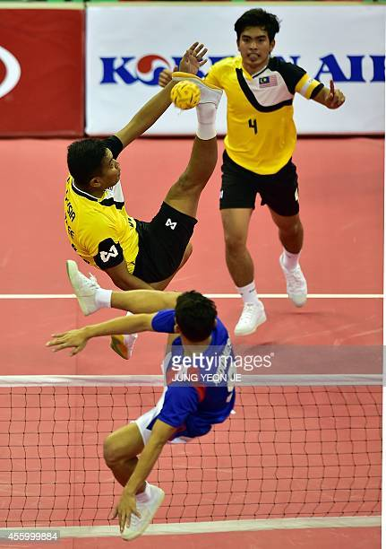 Malaysia's Zamree Bin Mohd Dahan strikes the ball against Indonesia Nofrizal in the men's team sepaktakraw preliminary match during the 2014 Asian...