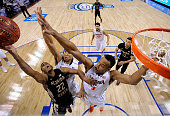 Malcolm Brogdon and Darion Atkins of the Virginia Cavaliers defend a shot by Xavier RathanMayes of the Florida State Seminoles during the...