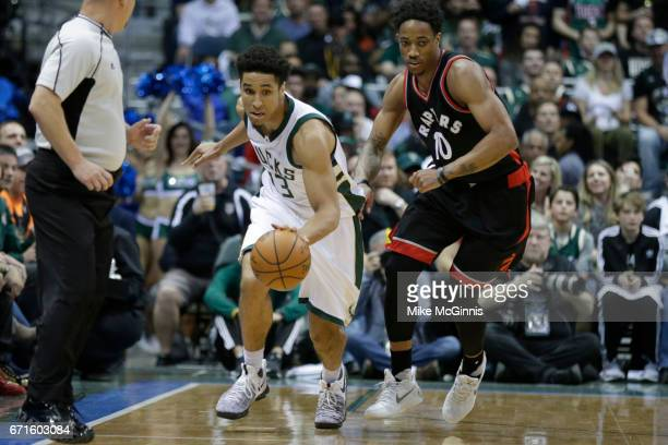 Malcolm Brogdon of the Milwaukee Bucks dribbles the basketball up the court with DeMar DeRozan of the Toronto Raptors defending during the first half...
