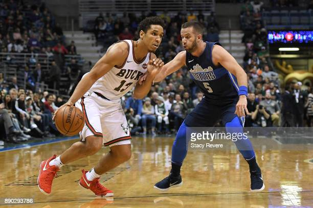 Malcolm Brogdon of the Milwaukee Bucks drives around JJ Barea of the Dallas Mavericks during a game at the Bradley Center on December 8 2017 in...
