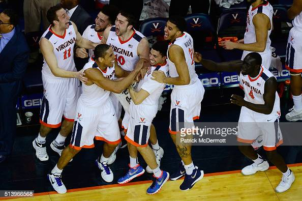 Malcolm Brogdon of the Virginia Cavaliers celebrates with his teammates after Caid Kirven made a threepoint field goal in the second half during...