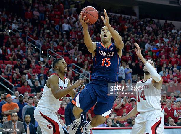 Malcolm Brogdon of the Virginia Cavaliers drives between Ralston Turner and Caleb Martin of the North Carolina State Wolfpack during a game at PNC...