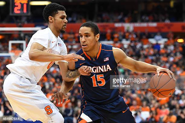 Malcolm Brogdon of the Virginia Cavaliers drives to the basket against the defense of Michael Gbinije of the Syracuse Orange during the first half at...