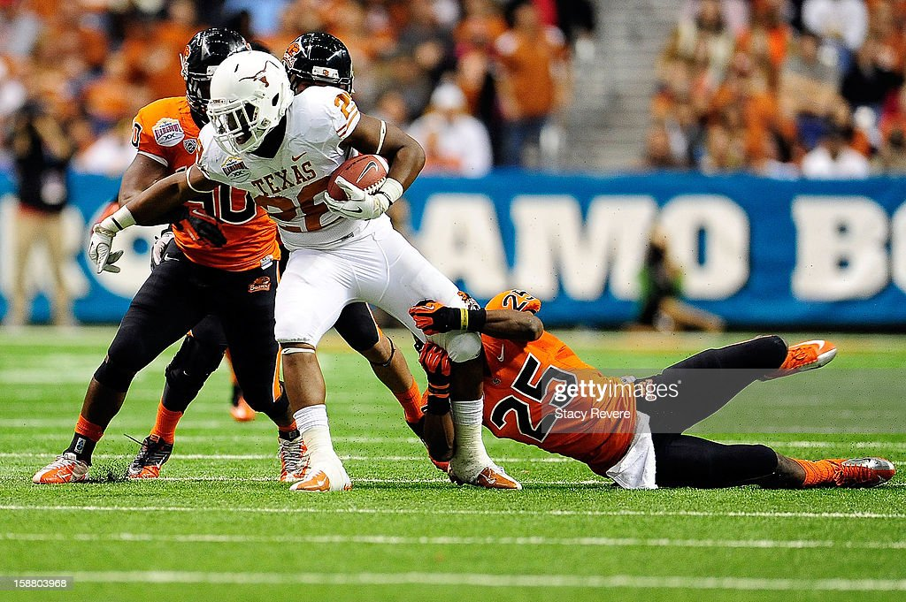 Malcolm Brown #28 of the University of Texas Longhorns is brought down by Ryan Murphy #25 of the Oregon State Beavers during the Valero Alamo Bowl at the Alamodome on December 29, 2012 in San Antonio, Texas. Texas won the game 31-27.