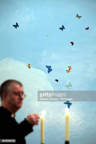 STANDALONE Malcolm Doney lights candles by a work at the new Damien Hirst exhibition featuring works inspired by religious images hosted at the New...