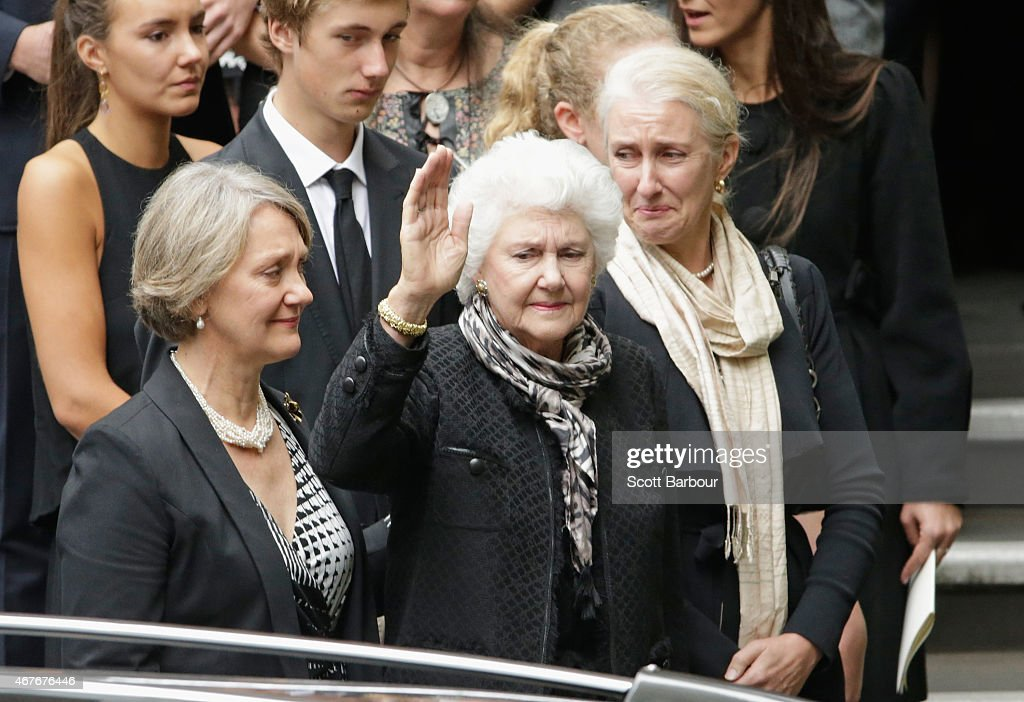 Malcolm Fraser's daughter Angela Marshall widow Tamie Fraser and daughter Phoebe WynnePope look on as the hearse leaves carrying the coffin at Scots...