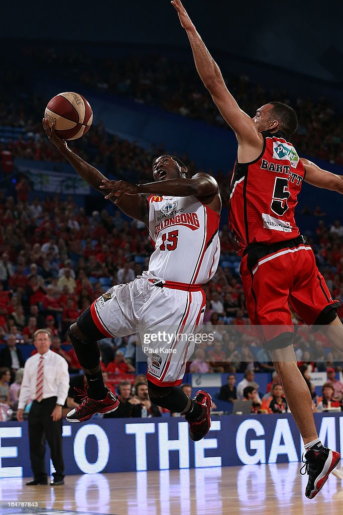 Malcolm Grant of the Hawks drives to the basket against Everard Bartlett of the Wildcats during game one of the NBL Semi Final Series between the Perth Wildcats and the Wollongong Hawks at Perth Arena on March 28, 2013 in Perth, Australia.