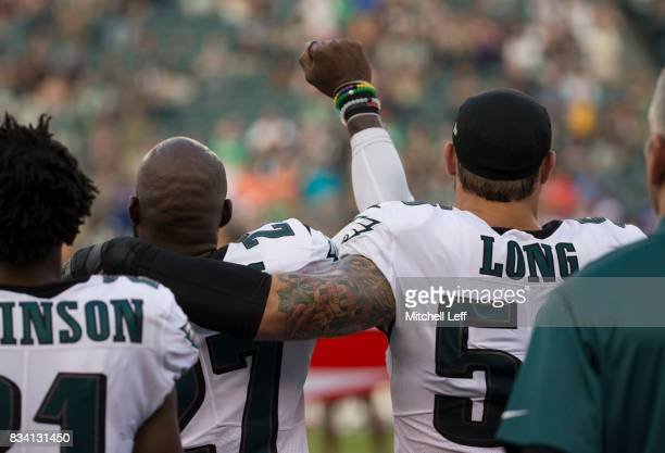 Malcolm Jenkins of the Philadelphia Eagles holds his fist in the air while Chris Long of the Philadelphia Eagles puts his arm around him during the...