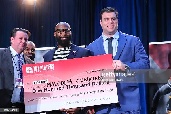 Malcolm Jenkins winner of the 2017 Byron Whizzer White Award poses with a $100000 check from Eric Winston President of the National Football League...