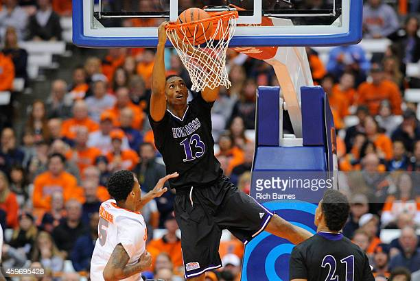 Malcolm Miller of the Holy Cross Crusaders dunks the ball over Chris McCullough of the Syracuse Orange during the second half at the Carrier Dome on...