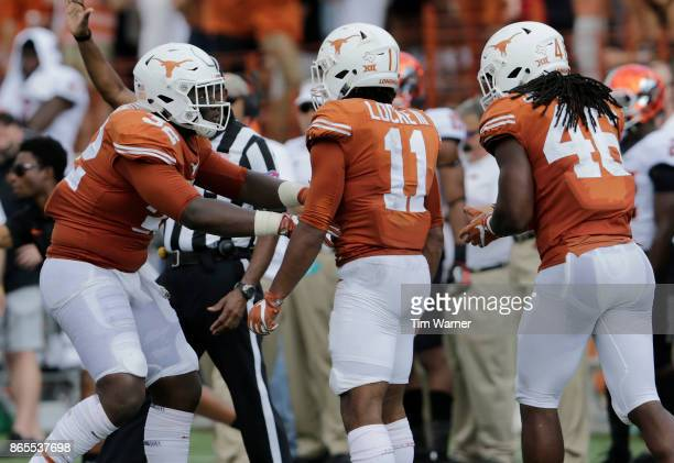 Malcolm Roach of the Texas Longhorns celebrates with PJ Locke III and Malik Jefferson after a tackle in the first half against the Oklahoma State...