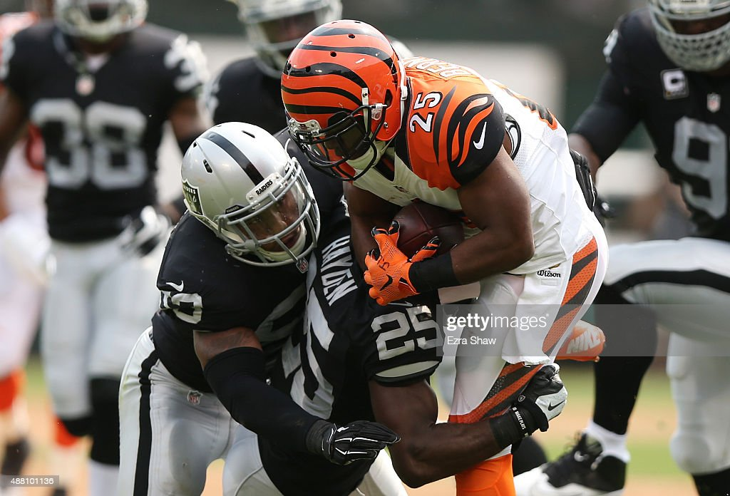 Malcolm Smith and DJ Hayden of the Oakland Raiders tackle Giovani Bernard of the Cincinnati Bengals during the first half of their NFL game at Oco...