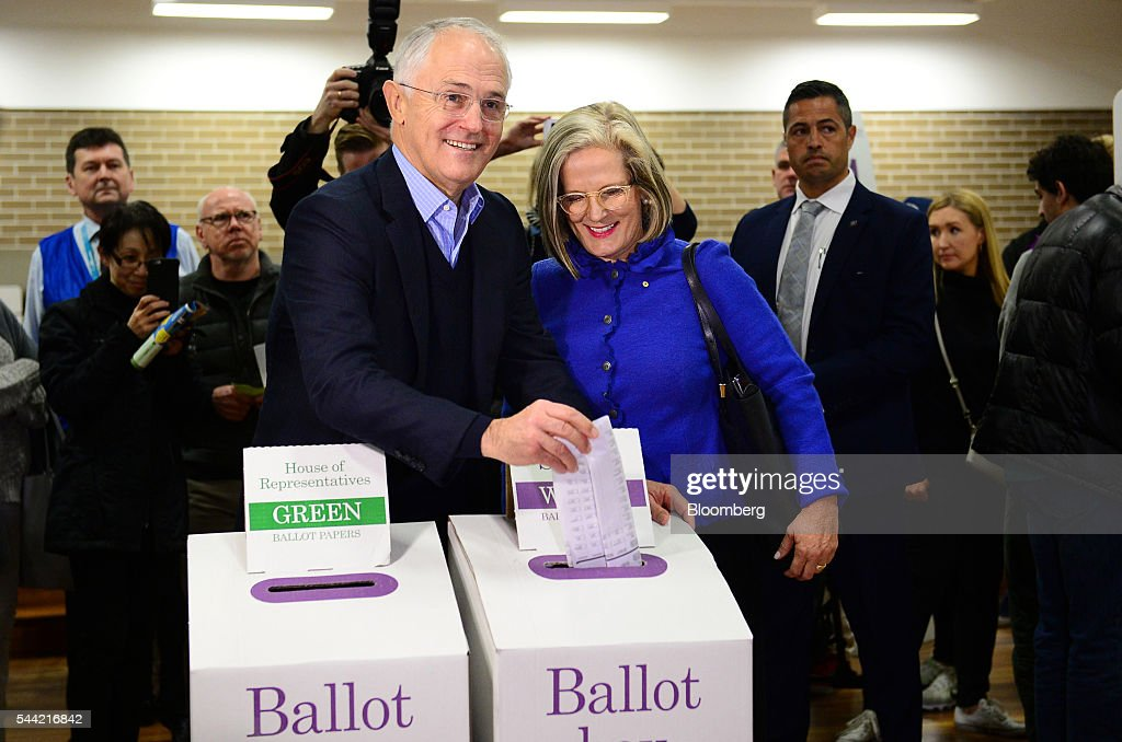Malcolm Turnbull, Australia's prime minister, center left, stands with his wife Lucy Turnbull as he casts his ballot at a polling station in Sydney, Australia, on Saturday, July 2, 2016. Turnbull is seeking another three-year term for his Liberal-National coalition in Australia's election Saturday, telling voters he can steer the world's 12th-largest economy through global headwinds and a fading commodities boom. Photographer: Jeremy Piper/Bloomberg via Getty Images