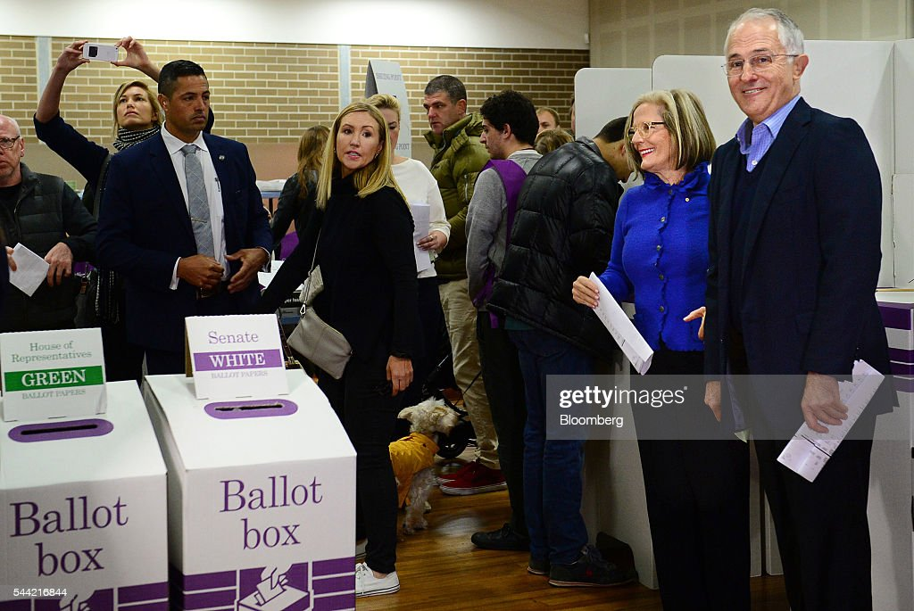 Malcolm Turnbull, Australia's prime minister, right, stands with his wife Lucy Turnbull, second right, after marking their ballots at a polling station in Sydney, Australia, on Saturday, July 2, 2016. Turnbull is seeking another three-year term for his Liberal-National coalition in Australia's election Saturday, telling voters he can steer the world's 12th-largest economy through global headwinds and a fading commodities boom. Photographer: Jeremy Piper/Bloomberg via Getty Images