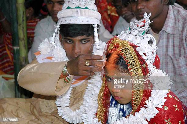 An Indian groom puts vermilion the holy mark belived the as sign of hindu marriage on the forehead of his underage bride during a mass marriage...