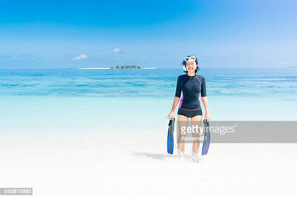 Maldives, Ari Atoll, young female diver coming out of water