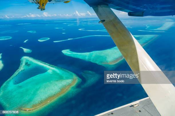 Maldives beach from birds eye view. Aerial view on Maldives island, atoll. Tropical islands and atolls in Maldives from aerial view. Summer holiday beach landscape background in Maldives.
