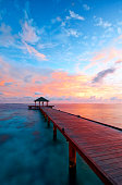 Dawn in the Maldives. A pier juts out into the tropical waters around the island of Vilamendhoo whilst, overhead, the sun turns the sky to spectacular reds & pinks. Various corals can be seen in the c