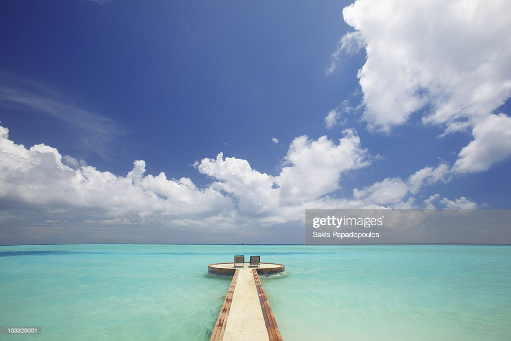 Maldives, jetty and chairs overlooking sea : Stock Photo