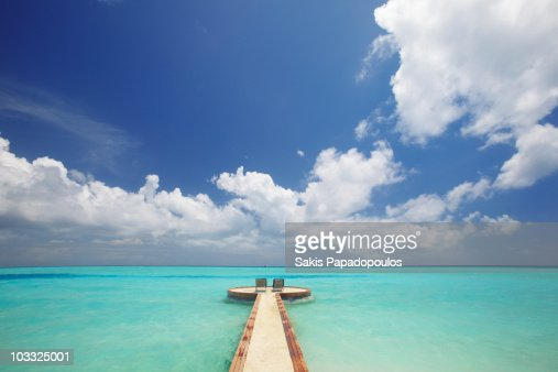 Maldives, jetty and chairs overlooking sea : Stockfoto