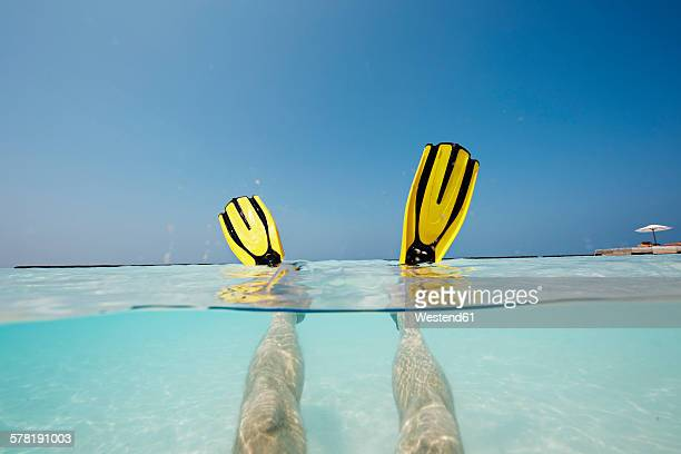 Maldives, mans feet with flippers in shallow water
