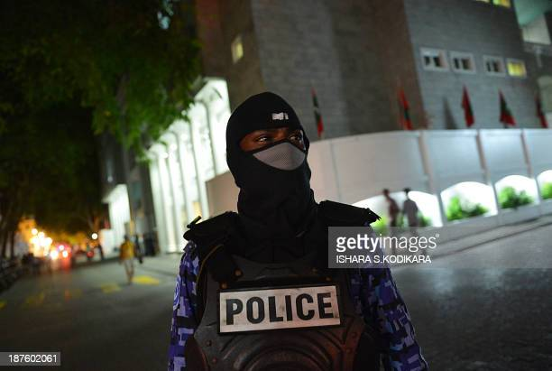 A Maldives police officer stands guard during a protest by supporters of former Maldivian president and presidential candidate Mohamed Nasheed in...