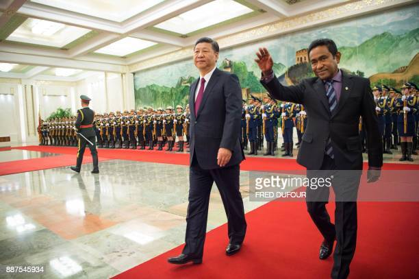 Maldives' President Abdulla Yameen and China's President Xi Jinping wave during a welcome ceremony at the Great Hall of the People in Beijing on...