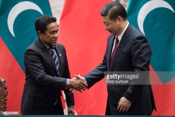 Maldives' President Abdulla Yameen shakes hand with China's President Xi Jinping after a signing ceremony at the Great Hall of the People in Beijing...