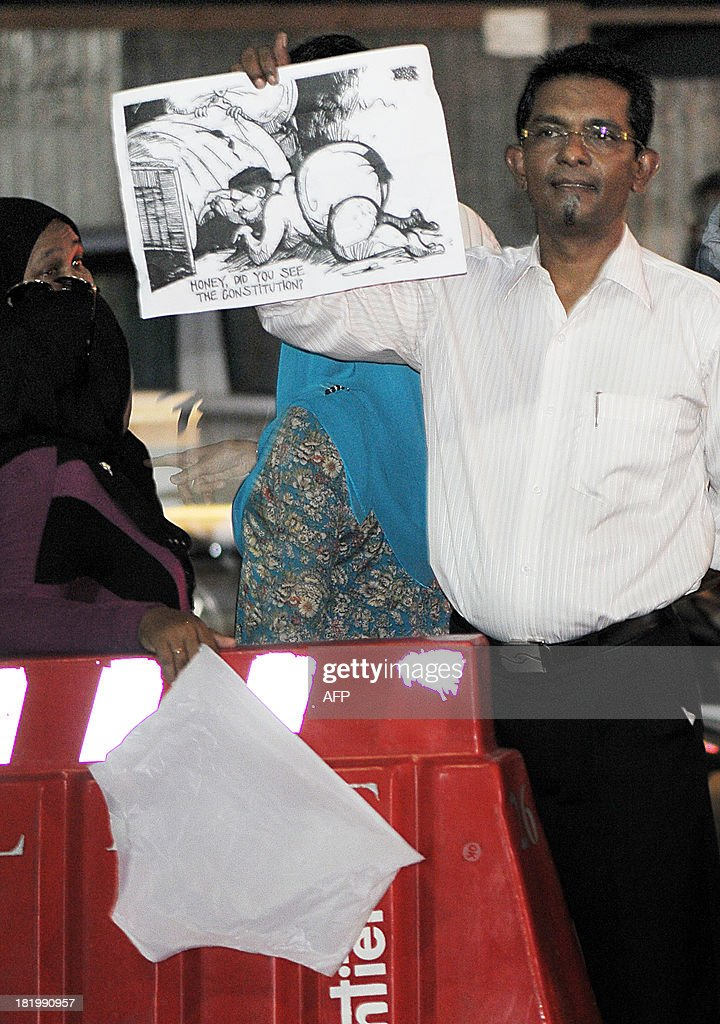 Maldivian activists wave underwear and cartoons as they stage a protest in Male late September 26, 2013. Police in the Maldives said that they had arrested 14 protesters involved in hanging white underpants outside a courthouse as a constitutional crisis over stalled elections on the honeymoon islands deepened. Supporters of the opposition Maldivian Democratic Party (MDP) been begun displaying white briefs in public to taunt Supreme Court judge Ali Hameed who was allegedly filmed during a sex romp in a video that has gone viral.