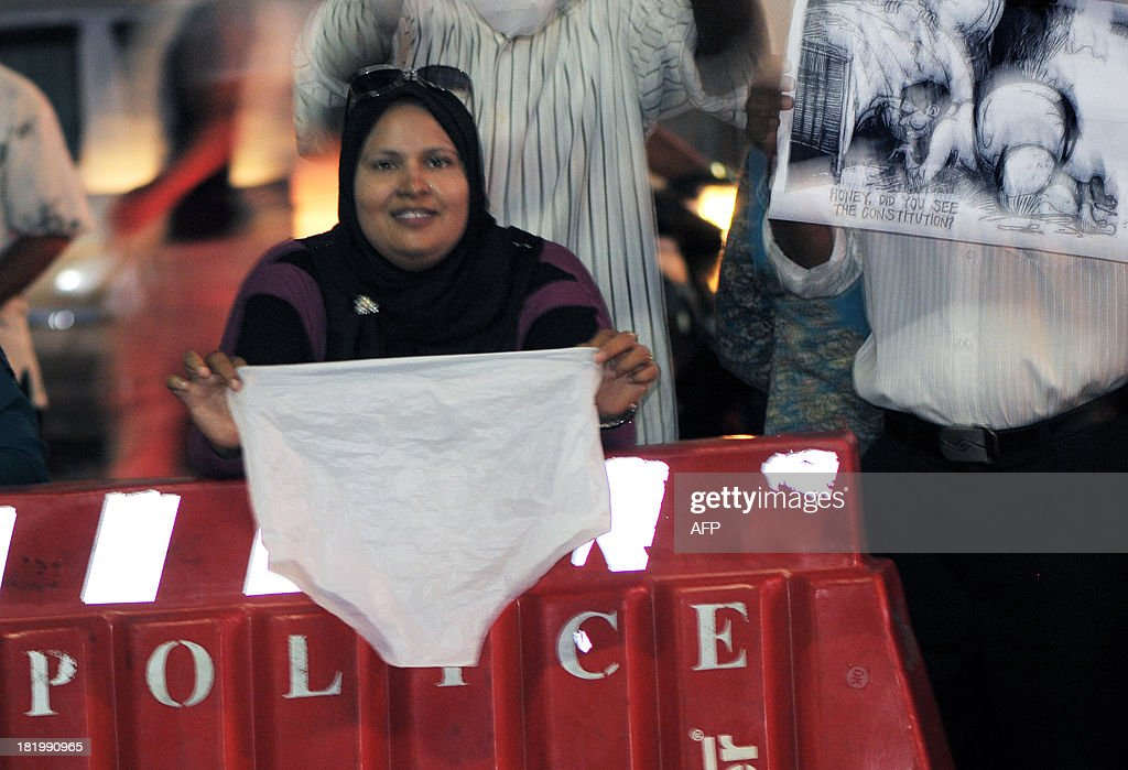 Maldivian activists wave underwear and cartoons as they stage a protest in Male late September 26, 2013. Police in the Maldives said that they had arrested 14 protesters involved in hanging white underpants outside a courthouse as a constitutional crisis over stalled elections on the honeymoon islands deepened. Supporters of the opposition Maldivian Democratic Party (MDP) been begun displaying white briefs in public to taunt Supreme Court judge Ali Hameed who was allegedly filmed during a sex romp in a video that has gone viral. AFP PHOTO/STR