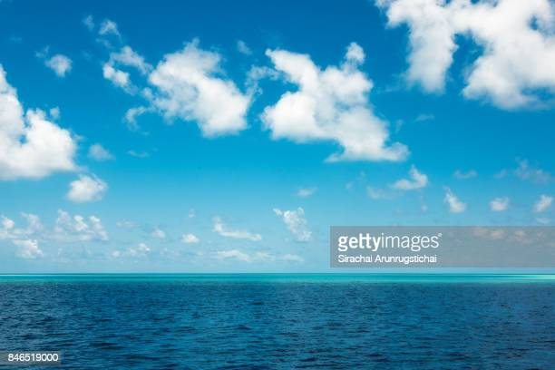 Maldivian atoll in deep blue sea under cloudy sky.