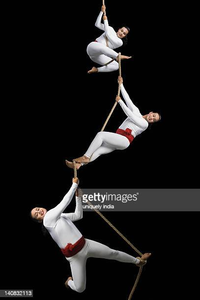 Male acrobats performing on a rope
