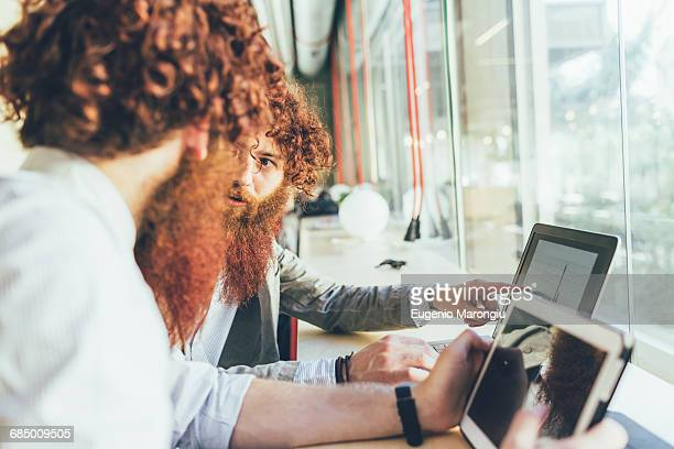 Male adult hipster twins pointing at laptop in office