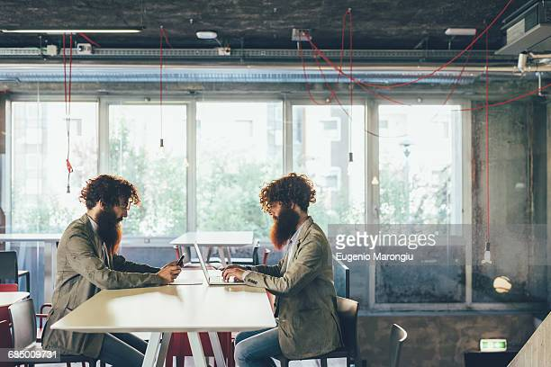 Male adult hipster twins sitting face to face at desk in office