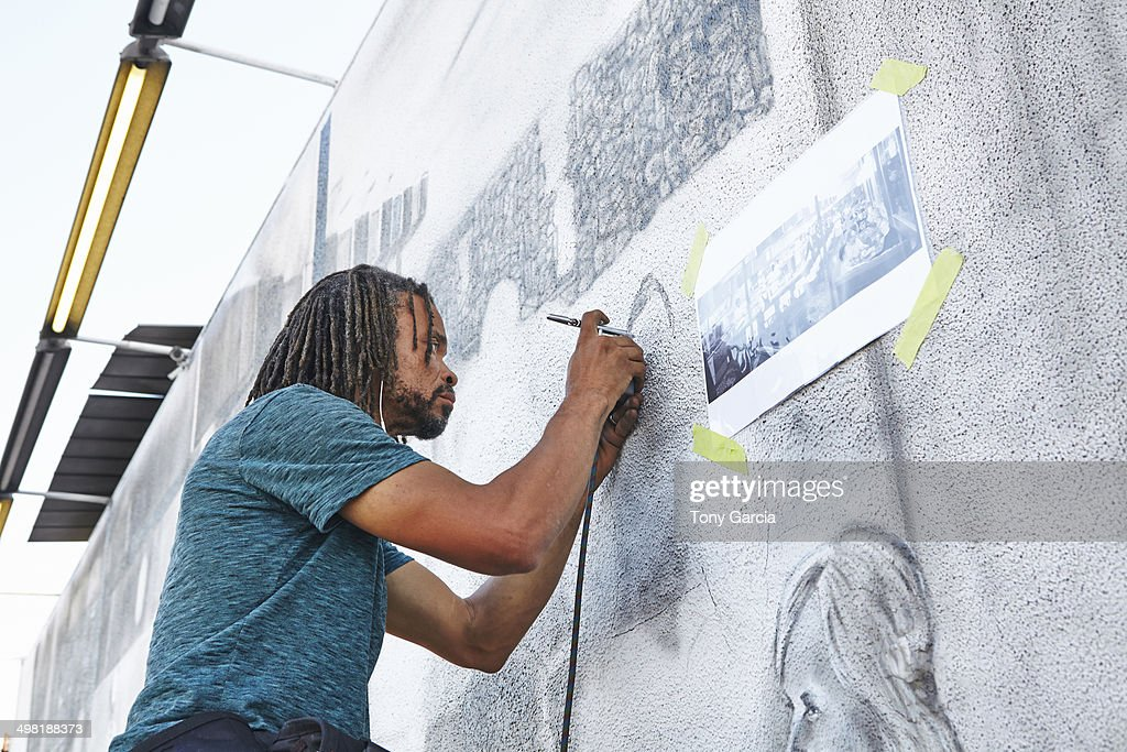 Male african american airbrush artist painting mural