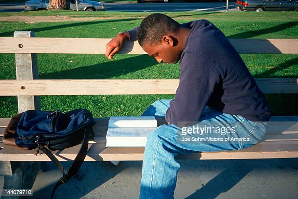 Male African American student studying on a bench Santa Monica California