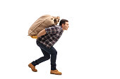 Full length profile shot of a male agricultural worker carrying a burlap sack on his back isolated on white background