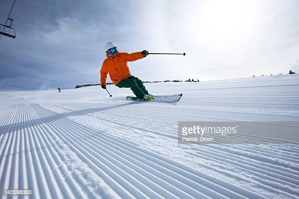 A male alpine skier smiles while skiing untracked groomers in Colorado.