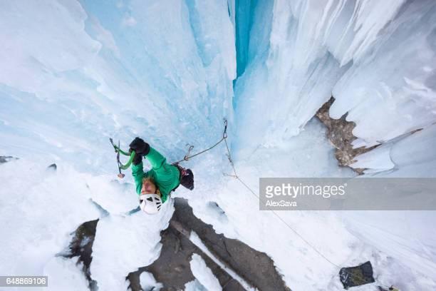 Male alpinist ice climbing on frozen waterfall