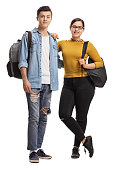 Full length portrait of a male and a female teenage student isolated on white background