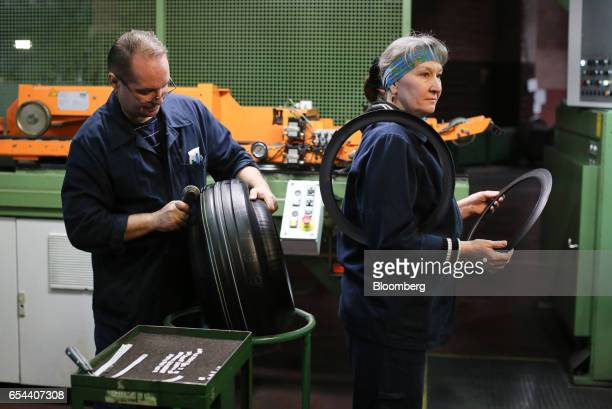 A male and a female worker prepares a 'green' tire after being shaped on a tireforming machine at the Belshina JSC tire factory in Babruysk Belarus...