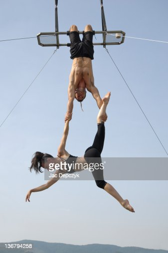 Male and female acrobats perform high on trapeze : Stock Photo
