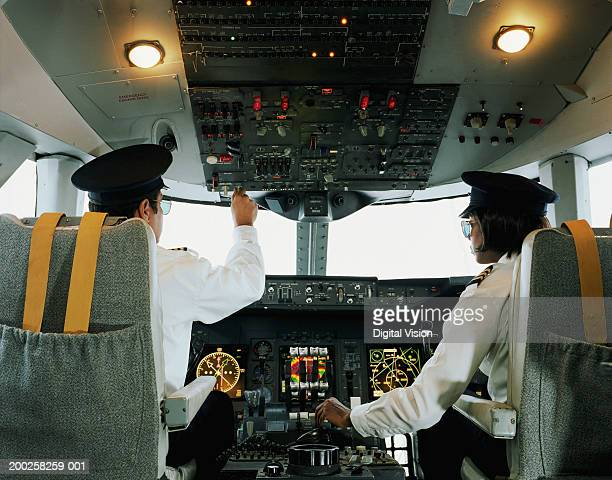 Male and female aeroplane pilot, operating controls, rear view