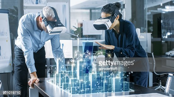 Male and Female Architects Wearing  Augmented Reality Headsets Work with 3D City Model. High Tech Office Professional People Use Virtual Reality Modeling Software Application. : Stock Photo