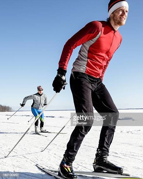 Male and female athletes cross-country skiing.