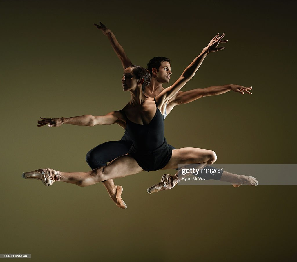 Male and female ballet dancers in mid air poses, arms extended : Stock Photo