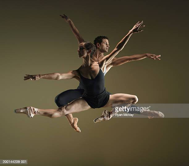 Male and female ballet dancers in mid air poses, arms extended