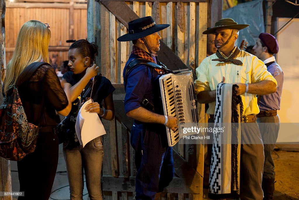 Male and female Brazilian Gaucho musicians and production team backstage talking and playing instruments practicing before the show at Reponte da...